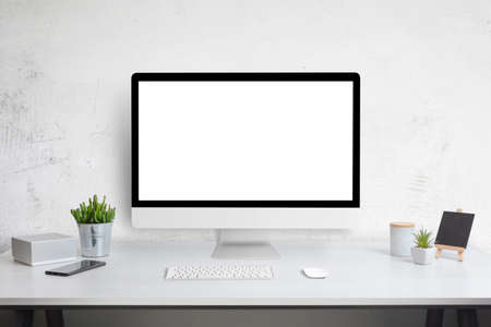 Computer display mockup on work desk. White work desk with plants, phone, box, keyboard and mouse. Web site design promotion template