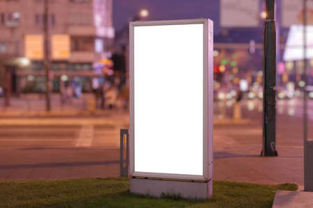Vertical billboard mockup on city street in the evening. Business buildings in the background