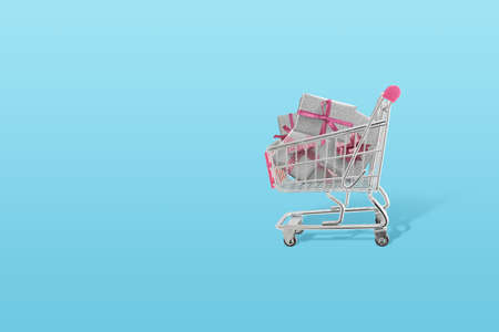 Concept of buying Christmas gifts. Shopping cart full of presents. Minimal concept with pastel colors
