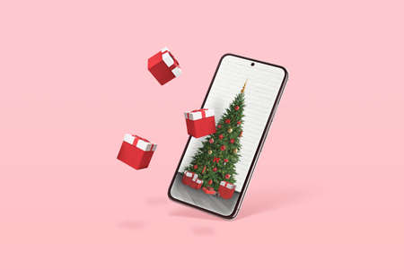 Phone with Christmas tree and gifts coming out of the display. Minimal concept with pastel pink color in background 版權商用圖片