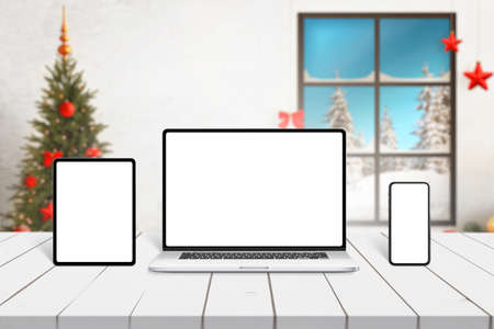 Laptop, tablet and smart phone mockup on white desk with Christmas decorations in background. Responsive design presentation template