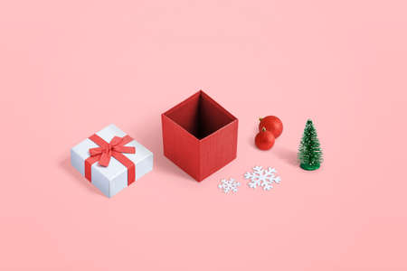 Cute opened Christmas gift box with several decorations on pastel pink background