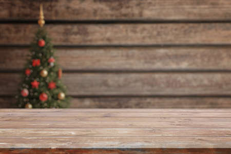 Empty wooden desk with christmas tree in background. Background for product presentation 版權商用圖片