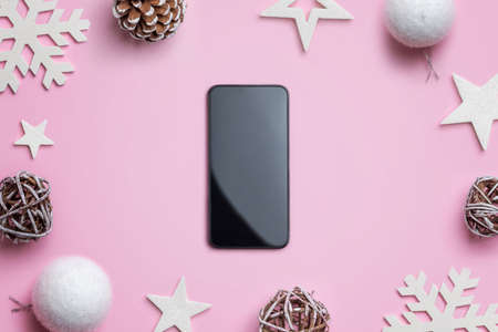 Phone on pink desk surrounded by Christmas decorations. Concept of Christmas shopping and gift wrapping. Blank smart phone for mockup 版權商用圖片