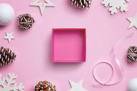 Open Christmas gift box on pink desk, surrounded by Christmas decorations. Concept of gift wrapping 版權商用圖片