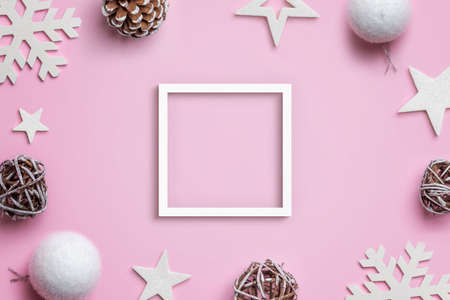 White frame surrounded by Christmas decorations on pink pastel desk. Top view, flat lay, composition