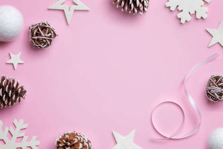 Christmas composition on pink desk. White stars, balls, snowflakes and cones. Christmas background. Top view, flat lay