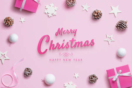 Merry Christmas and Happy New Year greeting card with Christmas decorations on pink pastel surface. Top view, flat lay