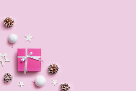 Christmas gift and decorations on pastel pink desk with copy space beside for greeting text. Top view, flat lay composition