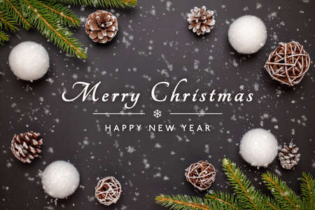 Merry Christmas and Happy New Year greeting card with decorations on black surface 版權商用圖片