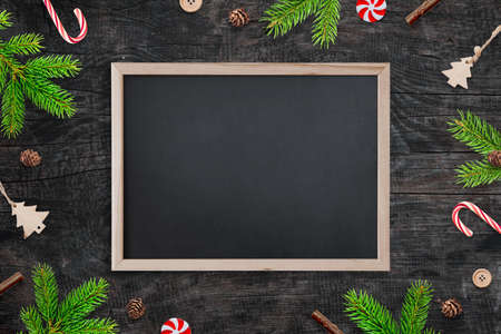 Blank chalkboard for greeting text surrounded by Christmas decorations. Top view, flat lay, composition on wooden table