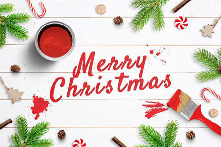 Merry Christmas painted with brush on white wooden surface and surrounded by Christmas decorations. Greeting card