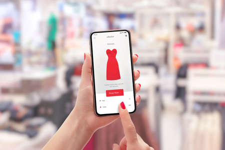 Girl buys a red dress with smart phone online. Clothing store in background concept