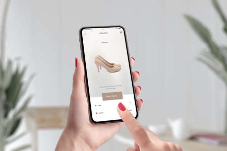 Shopping shoes online with e-commerce app concept. Woman holding smart phone and touch shop now button