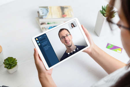 Online conference concept. Woman using tablet to make video call with business partner. 版權商用圖片