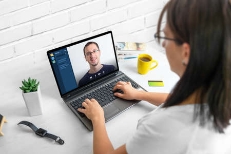 Online meeting with a teammate. The concept of working from home during an epidemic. A woman uses a laptop on work desk. 版權商用圖片
