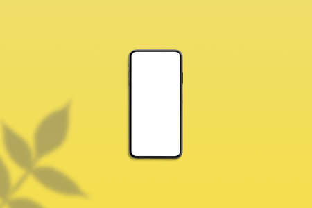 Phone mockup on yellow desk with plant shadow beside