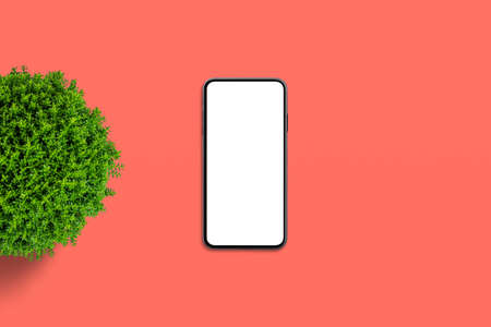 Phone and plant on red desk. Copy space beside. Flat, minimal composition. Top view, flat lay 版權商用圖片