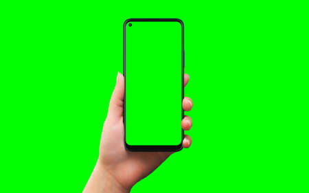 Phone in woman hand isolated in chroma key green 版權商用圖片