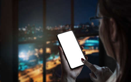 Woman use smart phone by the window. City lights in background. Isolated display for mockup, app design promotion