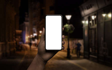 Phone mockup in woman hand. Night scene with city street in background