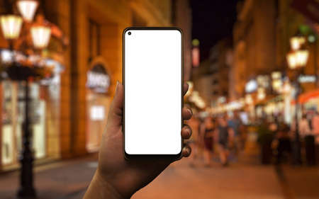 Phone mockup in woman hand at night. City street with lights in background 版權商用圖片