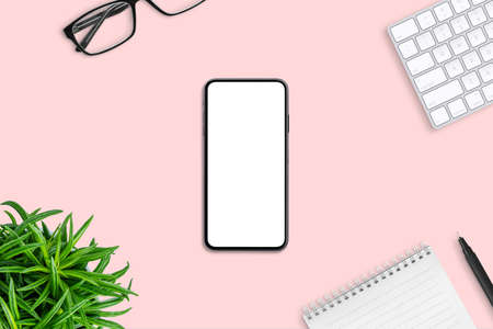 Phone with isolated screen on pink pastel desk surrounded by office supplies. Top view, flat lay composition. 版權商用圖片