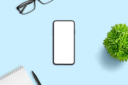 Phone mockup on blue office desk. Minimal composition with plant, pad, pen and glasses