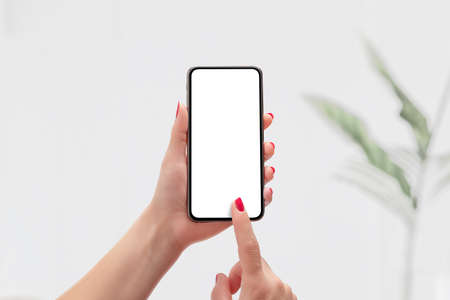 Phone mockup in woman hand. Isolated display for app promotion. Leaf of the plant is in the background Фото со стока
