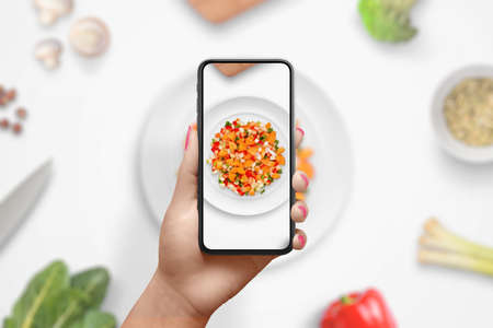 Photographing the preparation of a diet meal with vegetables with smart phone. Woman holding phone in vertical position