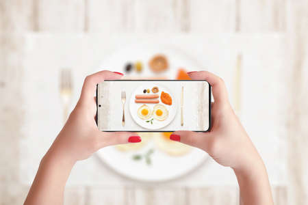 Taking photo of breakfast with phone. Woman holding smart phone in horizontal position Фото со стока