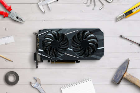 Graphic card service concept. Computer component on desk surrounded with repair tools Фото со стока
