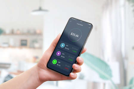 Cryptocurrency market value on smart phone app concept. Woman holding smart phone with Crypto wallet Фото со стока