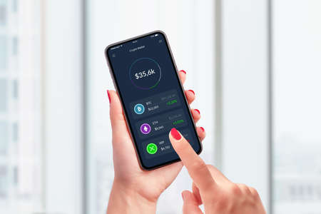 Value of cryptocurrencies in the wallet app concept. Smart phone in woman hands