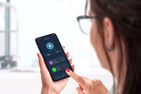 Concept of buying bitcoin cryptocurrency via a mobile application. Woman use smart phone with modern app