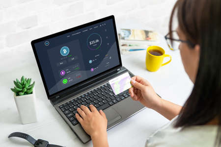 Woman buy bitcoins on a popular web page concept. Laptop with modern, flat design web page. Woman holding credit card