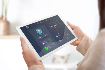 Cryptocurrency market web site concept on tablet in woman hands. Girl check bitcoin value