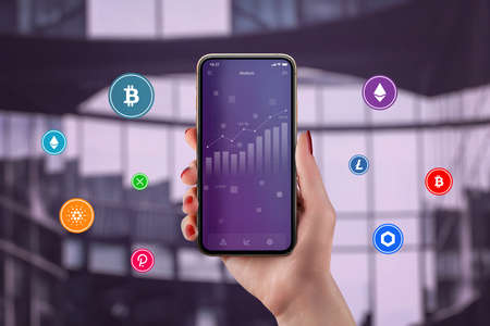 Concept of cryptocurrency market growth concept. Chart on smartphone in woman hand surrounded by cryptocurrencies