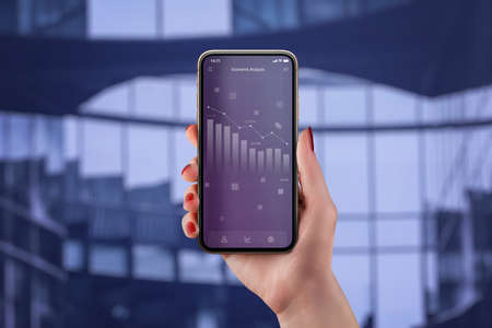 Economic analysis app concept with chart of the economic decline on smart phone in woman hand Фото со стока