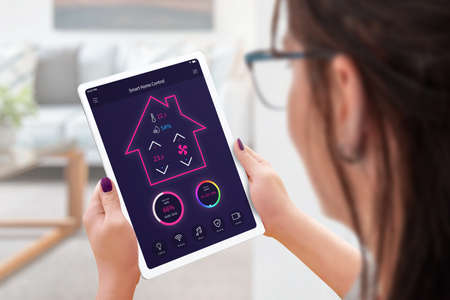 Woman with tablet controls a smart house, temperature, humidity, lighting and security