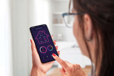Smart home control app concept on smart phone in woman hands Фото со стока