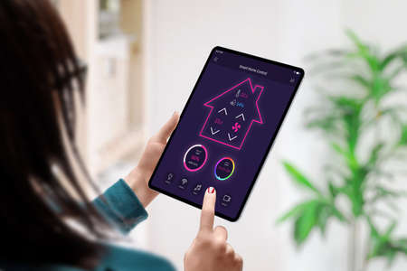 Smart home control app concept on tablet in woman hands. Home interior in background Фото со стока