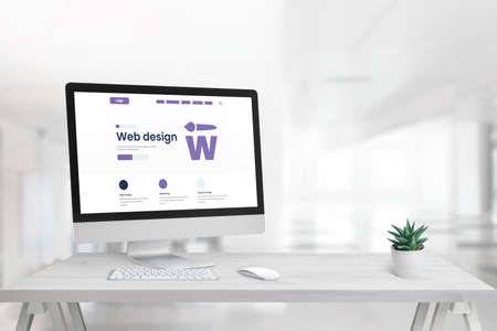 Web design studio with promo page on computer display and copy space beside
