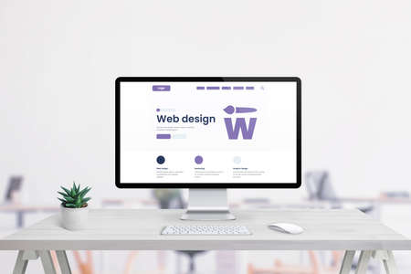 Web design agency promo page on computer display. Creative flat design promo page. Office interior in background Фото со стока