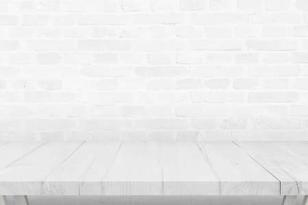 Empty white wooden desk and brick wall in background