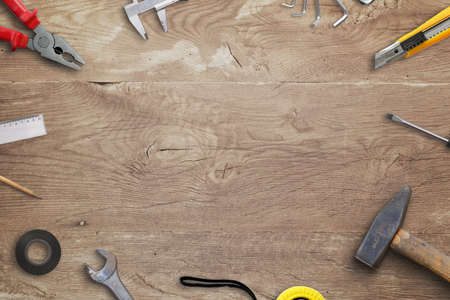 Wooden desk with tools and copy space in the middle. Handyman top view, flat lay composition Фото со стока