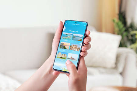 Choosing a travel destination with smart phone concept. Modern app with chose a trip option. Phone in woman hand. Close-up.