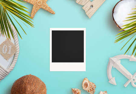 Blank old photo on blue surface surrounded by summer, beach objects. Vacation memories presentation mockup. Top view, flat lay composition Фото со стока