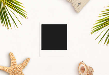 Photo paper on desk surrounded with summer, travel objects. Blank paper for mockup, vacation memories presentation. Palm leaves, starfish and shell. Top view, flat lay Фото со стока
