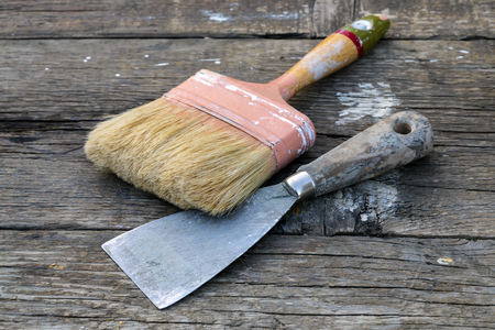 Old paintbrush and metal spatula on rustic wooden table.